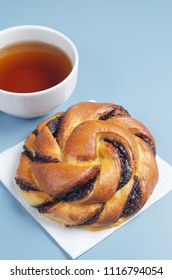 Bun with chocolate cream and cup of tea on the blue table close up