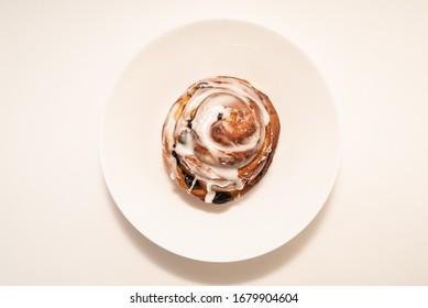 bun with raisins in white plate on white background