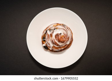 bun with raisins in white plate on black background