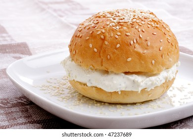 Bun with sesame on a white plate