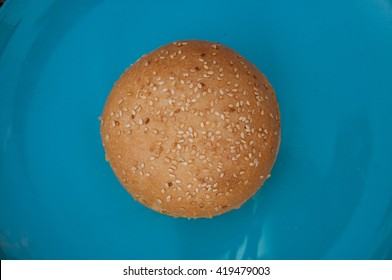 bun with sesame seeds on a plate top view