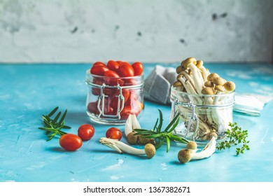 Buna Shimeji - edible mushroom from East Asia. Good food for good health. Clump of shimeji mushroom and cherry tomatoes in jars on blue concrete surface background