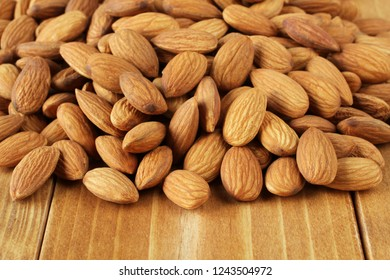 A bunch of almonds on brown toned wooden table. Closeup