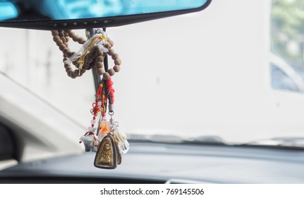A bunch of amulet hanging in the car,due to belief of asian people about good luck.