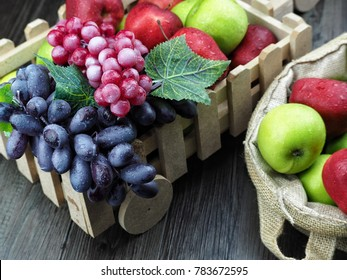 bunch of apples and grapes mixed in decorative basket. selective focus