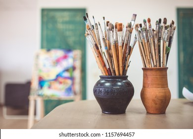 A bunch of art brushes standing in ceramic vases, on the table in the art studio