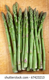 A bunch of asparagus tips on a wooden chopping board