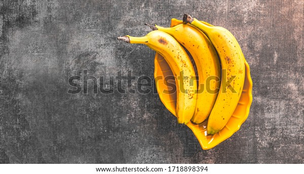 Bunch of bananas on a yellow, decorative plate. Three riped bananas in a bowl isolated on a grey background. Flat lay, top view