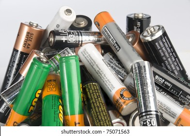 A bunch of batteries piled up disorderly for disposal. Isolated on white background.