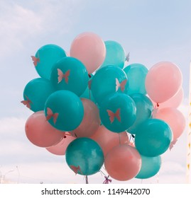 a bunch of beautiful pink and green balls, the color of the sea wave, with butterflies on them, against the backdrop of the sky