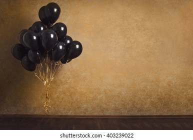 Bunch of black balloons on gold background. Stock photo.