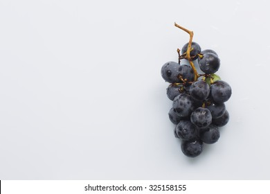 "Bunch of black grapes ""Isabella"" on a white background, natural light, view from the top"