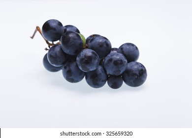 "Bunch of black grapes ""Isabella"" on a white background, studio lighting, the view from the top"
