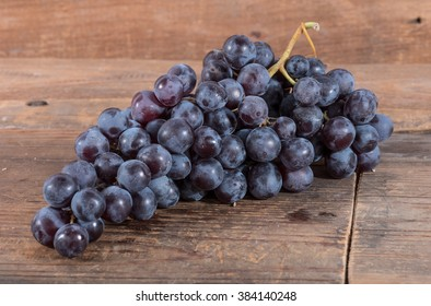 Bunch of black grapes, on wooden background