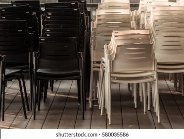 a bunch of black and white plastic chairs on wooden floor