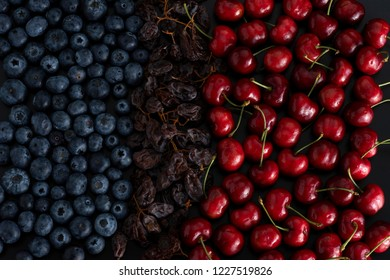 Bunch of blue berries, dried sultanas and cherries isolated on black background