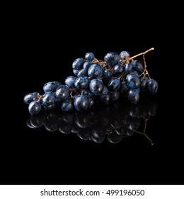 Bunch of blue grapes isolated on a black glossy background with realistic reflection