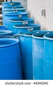 A bunch of blue rain barrels, setup in such a way to flow into each other, to collect rain water.