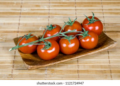 Bunch of branch tomatoes presented on bamboo tablet