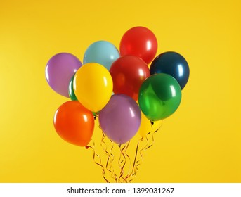 Bunch of bright balloons on color background. Celebration time