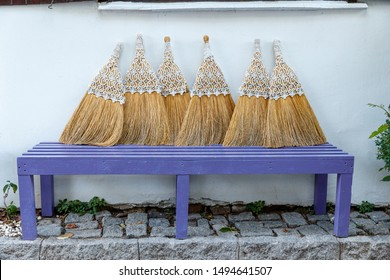 Bunch of brooms lean against the white wall of a house in Bozcaada