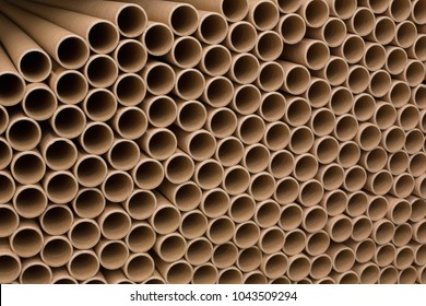A bunch of brown industrial paper core. A lot of paper cores or paper tubes. Brown paper rolls.