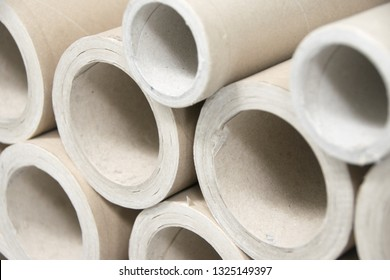 A bunch of brown industrial paper core isolated on white background with shadow reflection. A lot of paper cores or paper tubes on white backdrop. Brown paper rolls. - Image