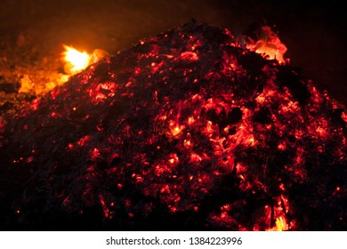 A bunch of burning coals with flashes of fire at night