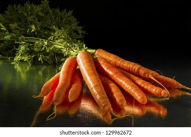 A bunch of carrots with greens and dark background