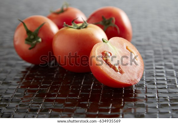 Bunch of cherry tomatoes with slices on dark stone background