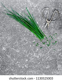 Bunch of chives on stone background, copy space, top view
