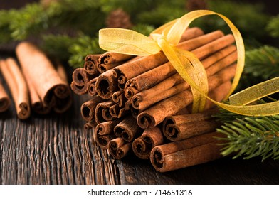 Bunch of cinnamon close up with fir tree on dark wooden background