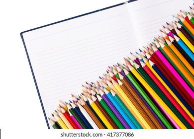 Bunch of color pencils on open notebook with copy space