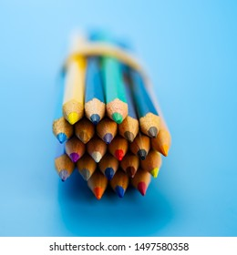 bunch of colored pencils lies on a blue background. Web banner, for your design.