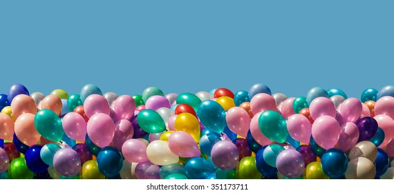 Bunch of colorful balloons border isolated on blue background