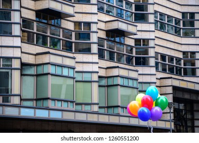 Bunch of colorful balloons on geometric shaped background of building facade in Berlin Germany. Contrast concept of edgy and smooth surfaces. Urban cityscape with bright balloons.