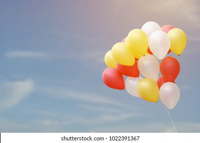 Bunch of Colorful Flying Balloons Forming Heart Shape with Blue Sky Background