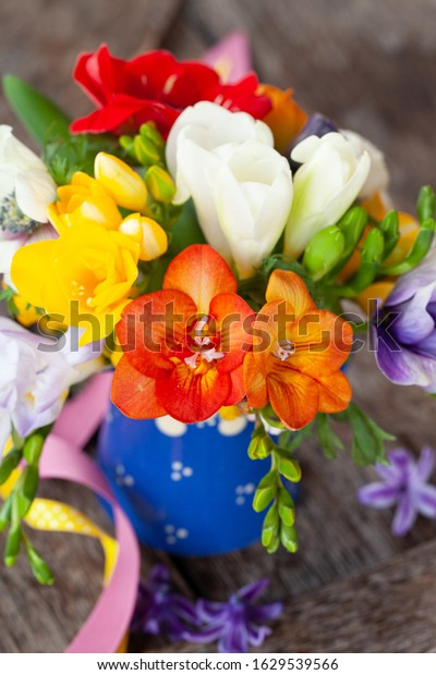 Bunch of colorful spring flowers in a little vase