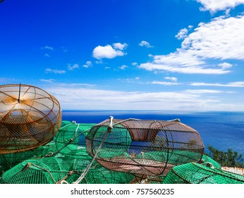 Bunch of crabs and lobsters fishing traps, made of wires and iron, against the blue Mediterranean Sea of the Amalfi Coast, Naples, Italy.