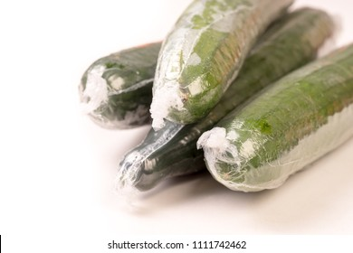 Bunch of cucumber wrapped in plastic films, isolated on white background