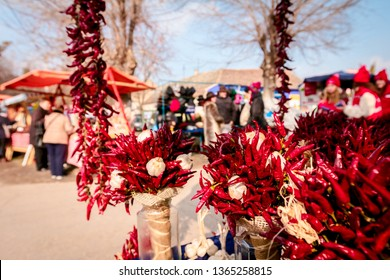 Bunch of decorated garlic and dried red hot peppers were placed at outdoor market place.