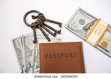Bunch of different keys, passport and money on a white background. New housing, property and mortgage loan concept. Copy space