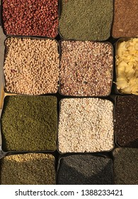 A bunch of different spices and grains for sale at a market.
