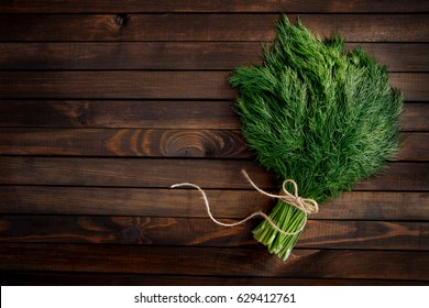 Bunch of dill isolated on a wooden background with space for text. Top view. Selective focus. Food for vegetarians