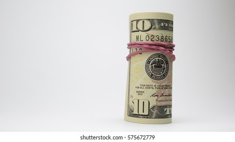 Bunch of dollars on the stack of dollars with red gum elastic band