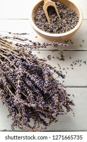 Bunch of dried lavender herbs resting on painted white wood planked table, with bowl of flower buds and woden scoop in soft focus background..