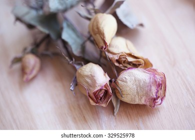 Bunch of dried pink flowers on wooden table