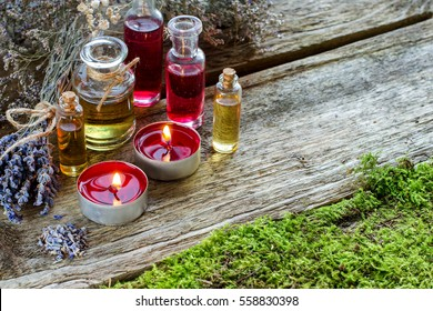 Bunch of dry lavender. Candles. Glass bottles aroma essential oils or Spa or natural aromatic oil on the old boards with moss, Spa or alternative meditation fragrance. Selective focus.