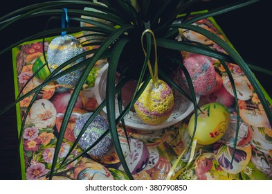 a bunch of easter eggs on the table, hanging on a flower