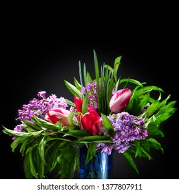 Bunch of flower over black background. Lilac, tulips and green grass. Floral bouquette isolated over black background
